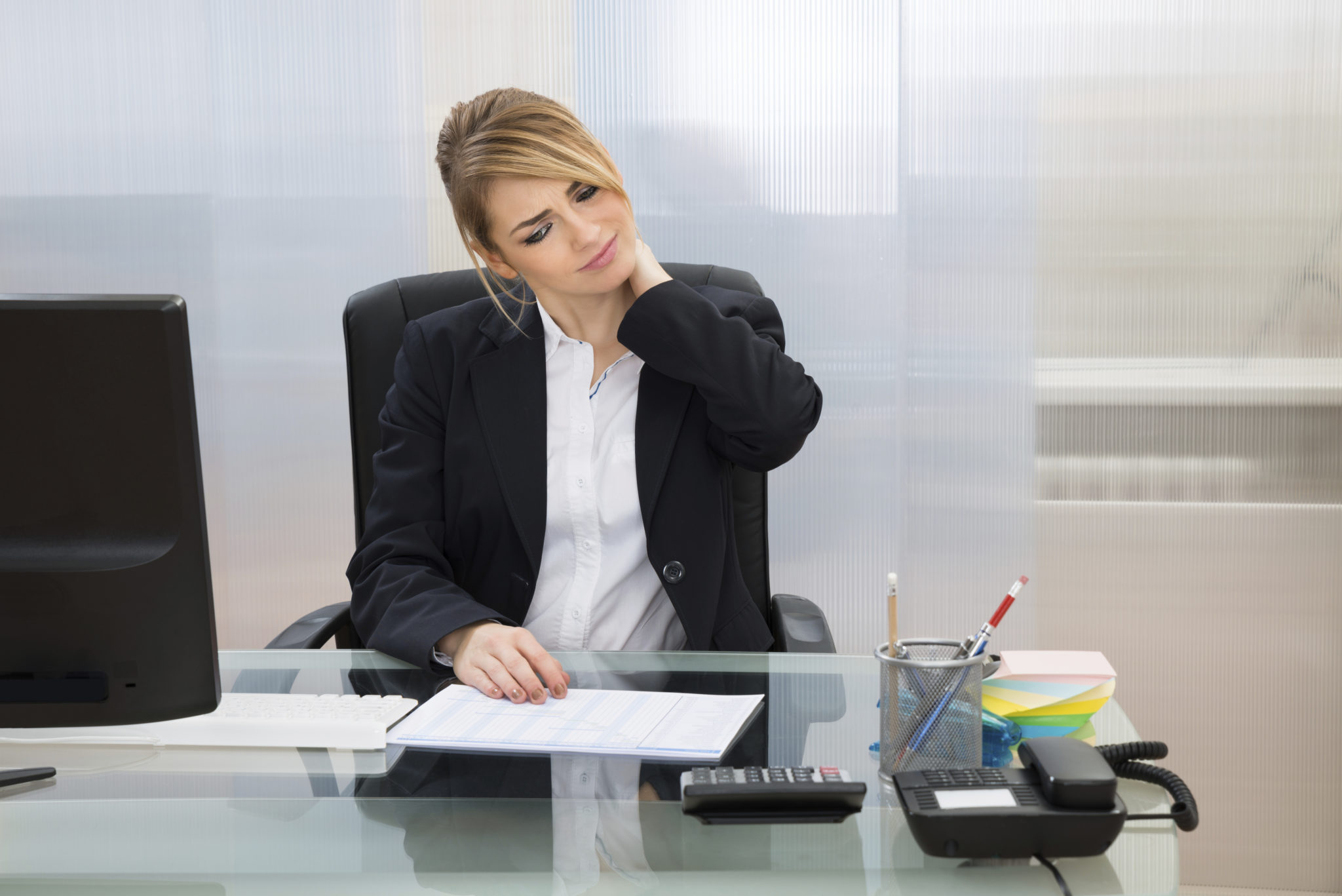 Portrait Of Young Businesswoman Suffering From Neckache In Office
